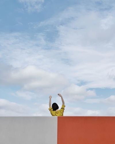 Rear view of woman with arms raised on building against sky