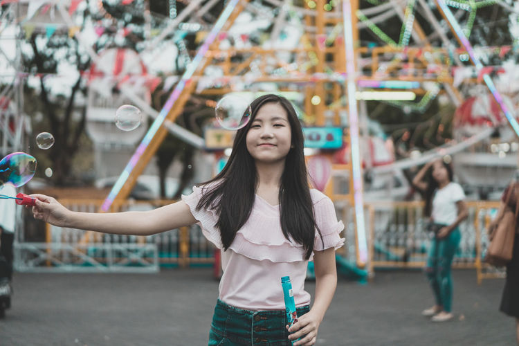 Portrait of young woman playing with bubbles at amusement park