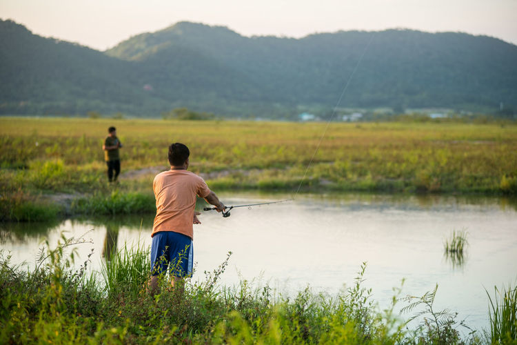 Fishing Countryside Field Fisherman Fishing Fishing Rod Fishing Time Folkways Free Time Green Growth Hobby Lake Lakeside Landscape Landscapes Men Mountains Nature Outdoors Plant Recreational Pursuit Scenic Tranquility Water Weekend Activities