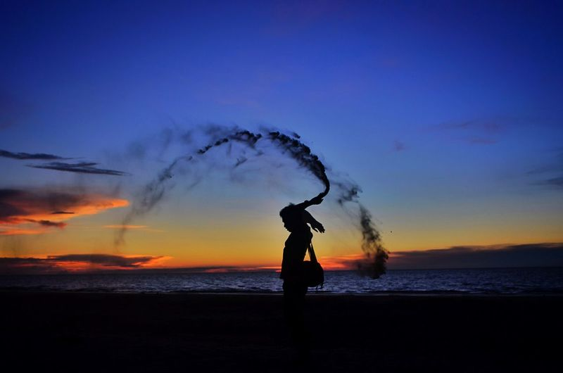 Silhouette man with smoke bomb standing at beach during sunset