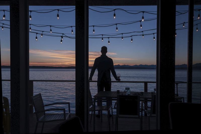 Silhouetted man enjoying red wine on sea view deck at sunset under hanging lights.