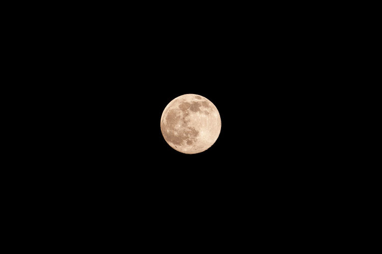 Low angle view of full moon against sky at night