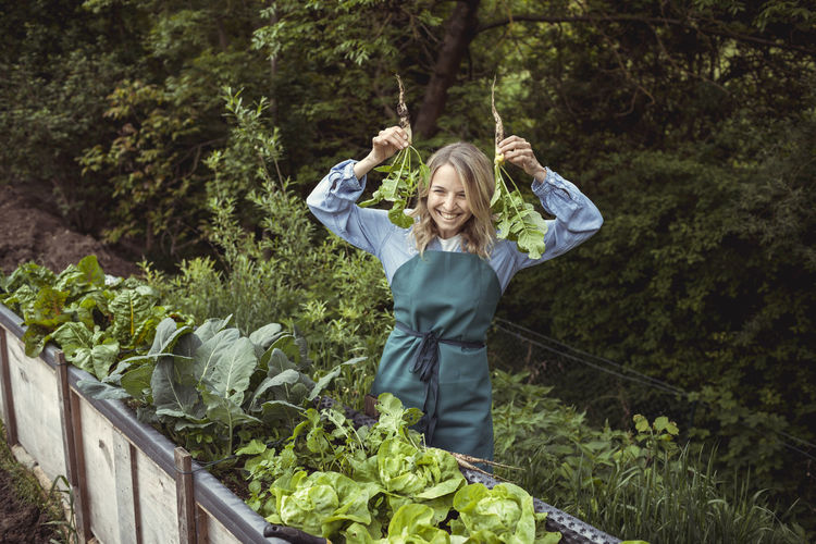 Full length portrait of a smiling young woman standing against plants
