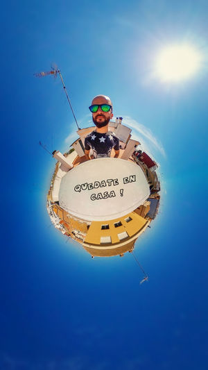 Low angle view of person against blue sky