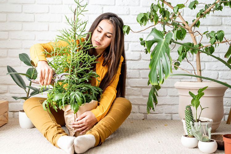 Young woman sitting in potted plant