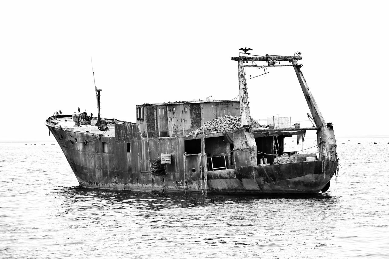damaged, abandoned, nautical vessel, obsolete, sea, clear sky, water, run-down, sinking, transportation, destruction, waterfront, bad condition, day, no people, outdoors, sky, nature, sunken