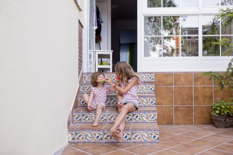 Sisters feeding watermelon to each other against house