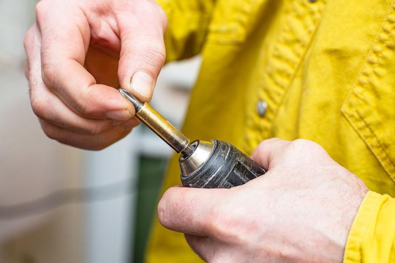Close-up of man holding screwdriver