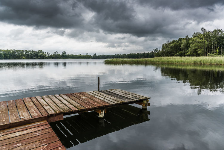 Old wooden pier on a lake in a cloudy summer day Beauty In Nature Cloud - Sky Day Lake Nature No People Outdoors Reflection Scenics Sky Tranquil Scene Tranquility Tree Water Waterfront Wood - Material