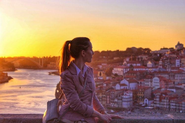 Woman standing by cityscape against sky during sunset