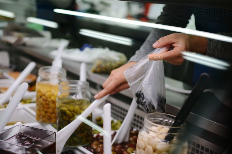 Cropped hand of person packing food in plastic bag at store