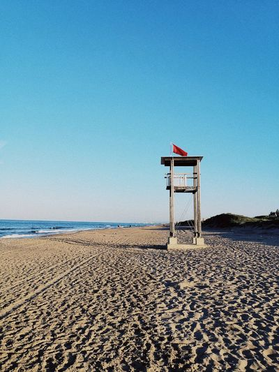 Lifeguard hut on beach against clear sky