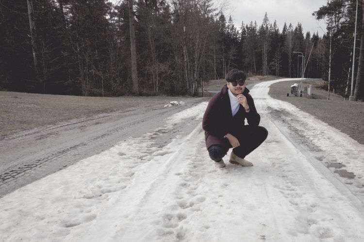 Woman on road in forest during winter