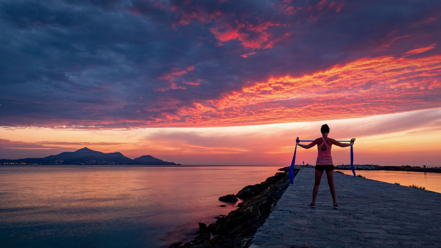 Strong confidence woman doing workout under the sunrise at seaside Sunset Sky Beauty In Nature Water Standing Orange Color Real People Scenics - Nature Lifestyles One Person Leisure Activity Full Length Tranquility Sea Idyllic Nature Cloud - Sky Tranquil Scene Non-urban Scene Human Arm Outdoors Arms Raised Workout Stretching Yoga Fitness