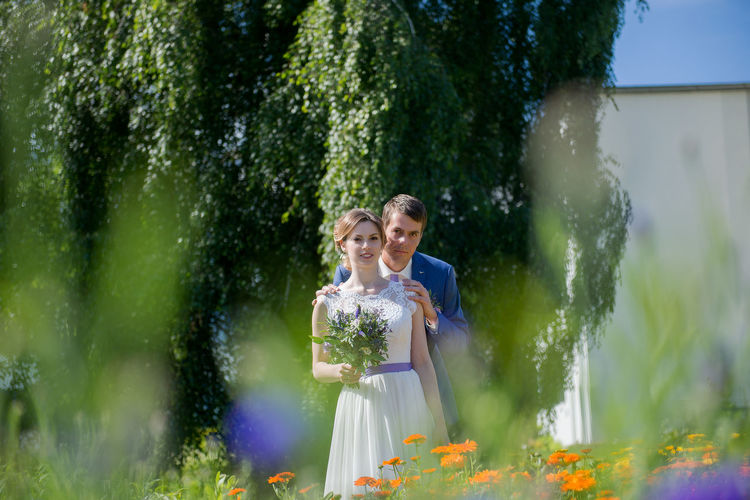 Bride And Groom Seen Through Plants At Park