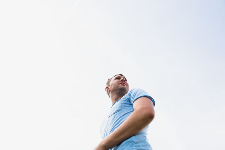 Low angle view of young man looking up against clear sky