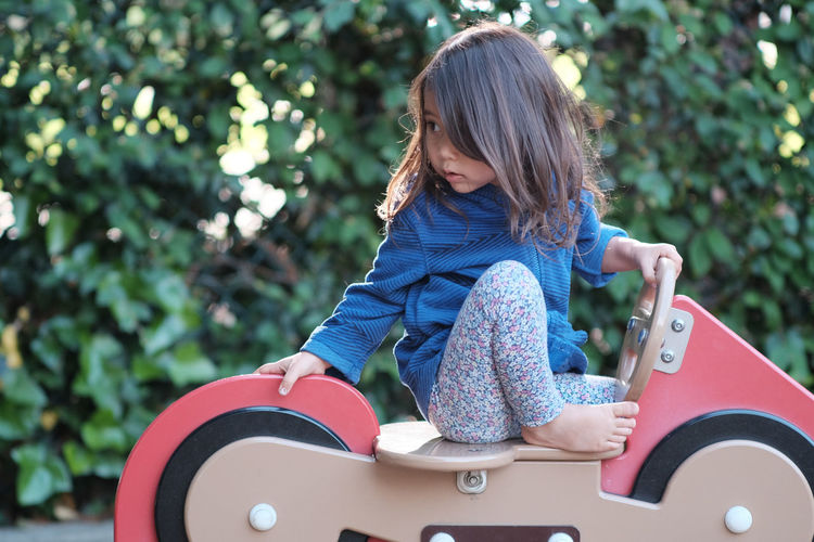 Girl looking away while sitting on spring ride at park