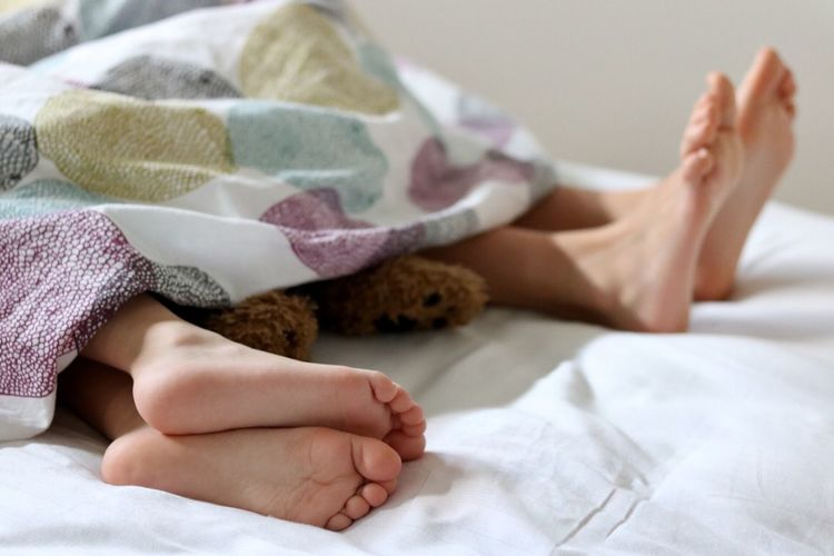 Low Section Of Couple Sleeping In Bed