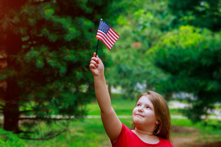 Cute overweight girl with small american flag standing at public park