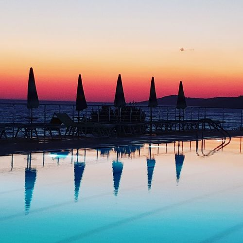 Silhouette swimming pool by sea against sky during sunset