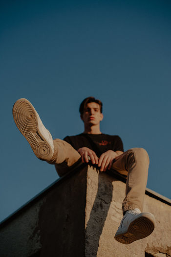 Low angle view of boy against clear blue sky