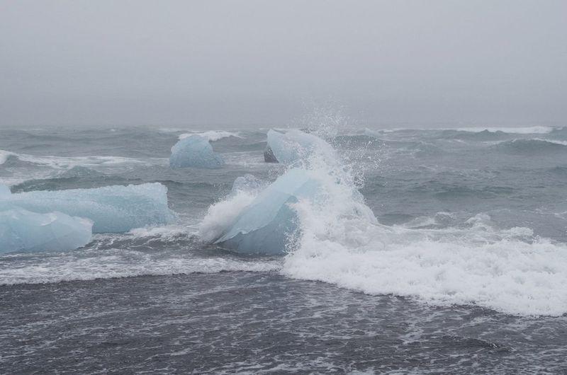 Iceberg in sea against sky