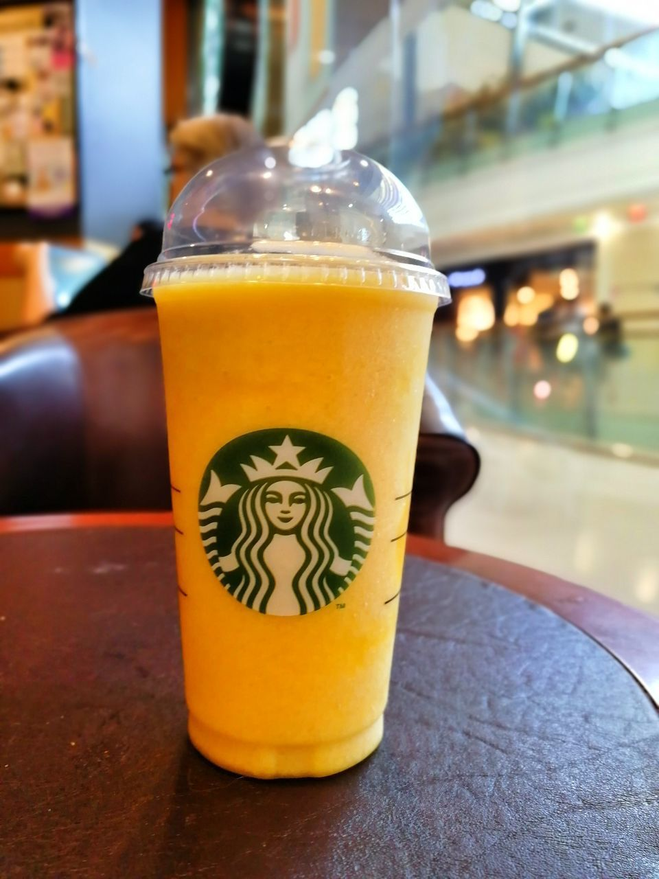 CLOSE-UP OF YELLOW DRINK ON TABLE