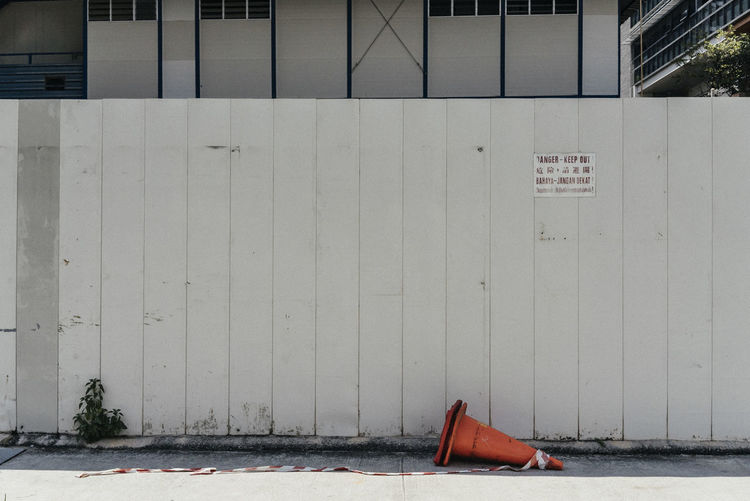 Traffic cone on road against wall