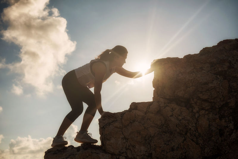 Low angle view of woman climbing rock formations against sky during sunny day