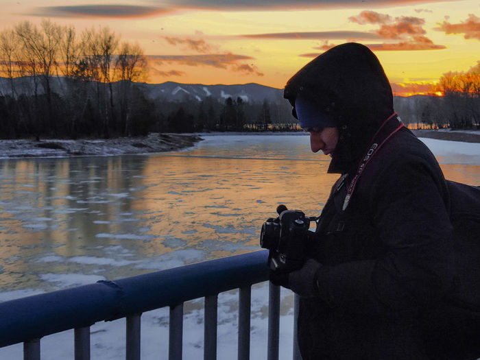 Side view of man photographing by lake during sunset