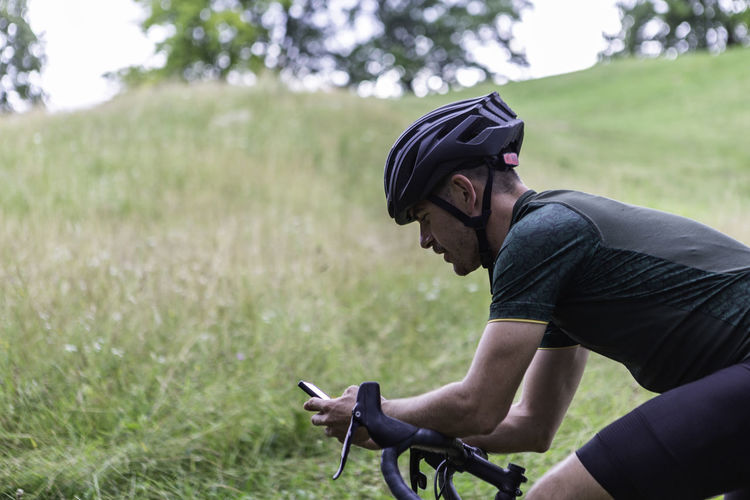 Man riding bicycle while using mobile phone outdoors