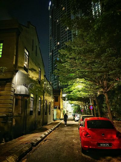 Vehicles on street amidst buildings in city at night