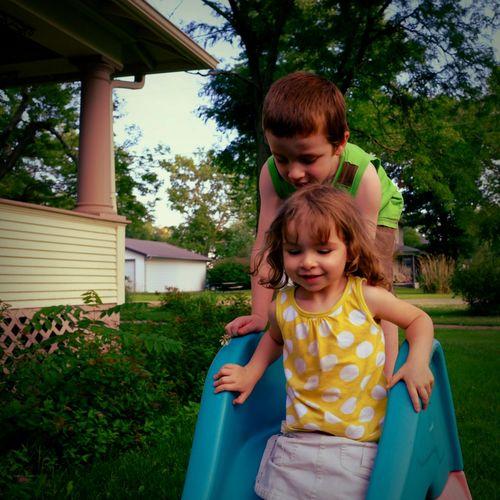 Cute siblings playing on slide at park