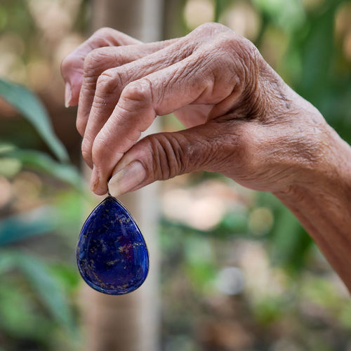 Cropped hand holding blue stone