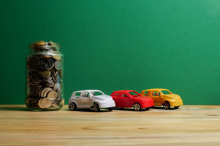 Abundance Auto Car Colored Background Copy Space Finance Financing Green Background Green Color Indoors  Jar Large Group Of Objects Mode Of Transportation No People Saving Savings Still Life Studio Shot Table Toy Toy Car Wood - Material
