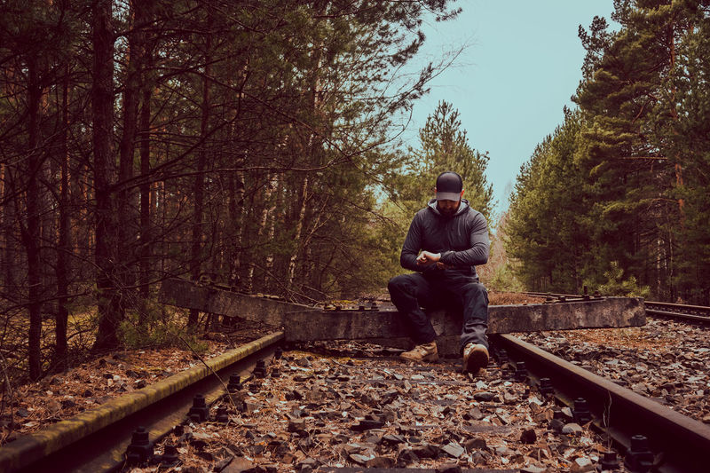 Rest on broken rails Adventure Beauty In Nature Break Destination Disconnected Explorer Forest Hiking Journey Nature One Man Only Outdoor Clothing Outdoors Rails Rear View Rest Resting Road Sitting Sports Clothing Traveler Trekking Wanderer