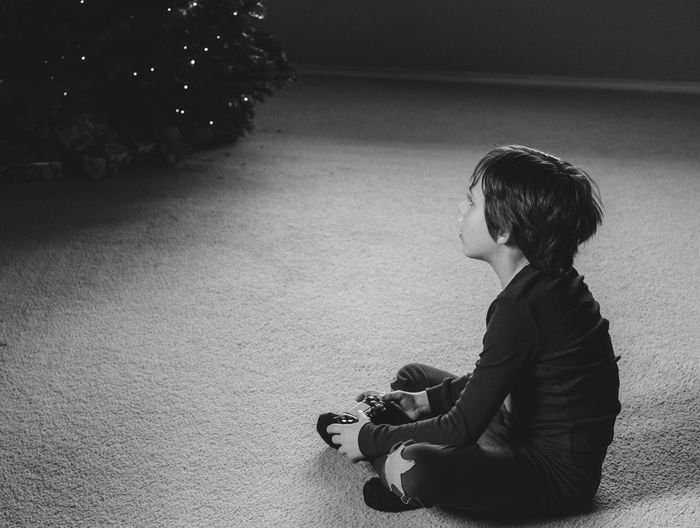 Casual Home Black And White Casual Clothing Child Childhood Elementary Age Full Length Game Controller Indoors  Leisure Activity Monochrome One Boy Only One Person Playing Video Games Real People Sitting Wireless Technology