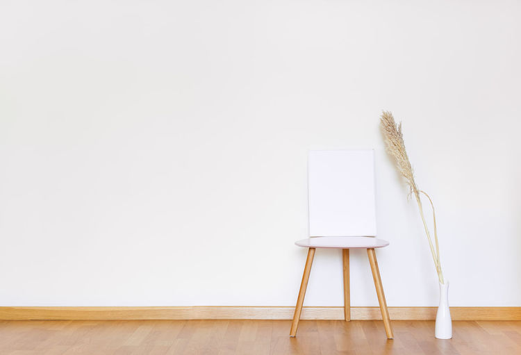 Empty chair on table against white background