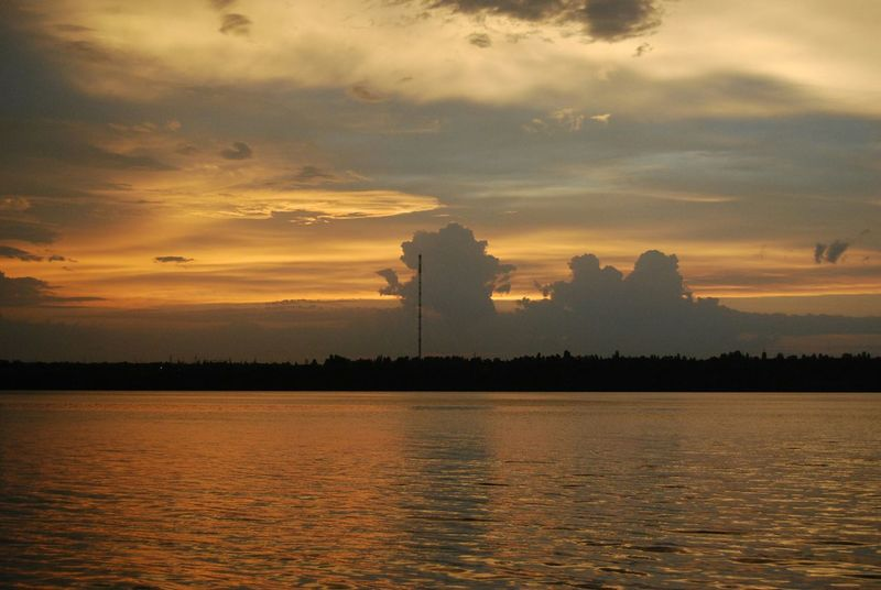 Sunset Outdoors Water Nature No People Sky Dinosaur Cloud Sunset Collection Marvelous View Sunset Silhouettes Sunset Clouds And Sky Sunset Clouds Cloudscape Riverbank River And Sky Capture The Moment