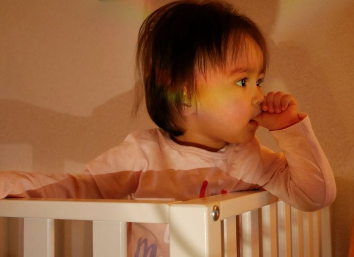 Close-up of cute girl sucking thumb while sitting in crib at home