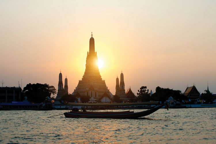 Wat Arun Ratchawararam Ratchawaramahawihan Temple of Dawn with Long-tail boat at sunset Sky Built Structure Architecture Sunset Building Exterior Religion Water Belief Place Of Worship Travel Destinations Building Nature Waterfront Travel Spirituality Tourism Silhouette No People Outdoors Wat Arun Ratchawararam Ratchawarama Temple Of Dawn Long-tail Boat