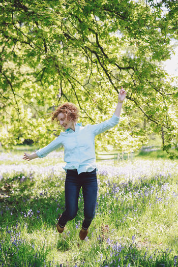 Blonde Blubells Blue Jeans Bluebell Casual Clothing Curly Hair Full Length Girl Grass Green Color Growth Jump Leisure Activity Lifestyles Nature People And Places Outdoors Park Plant Shirt Spring Tranquil Scene Tranquility Tree Natural Light Portrait
