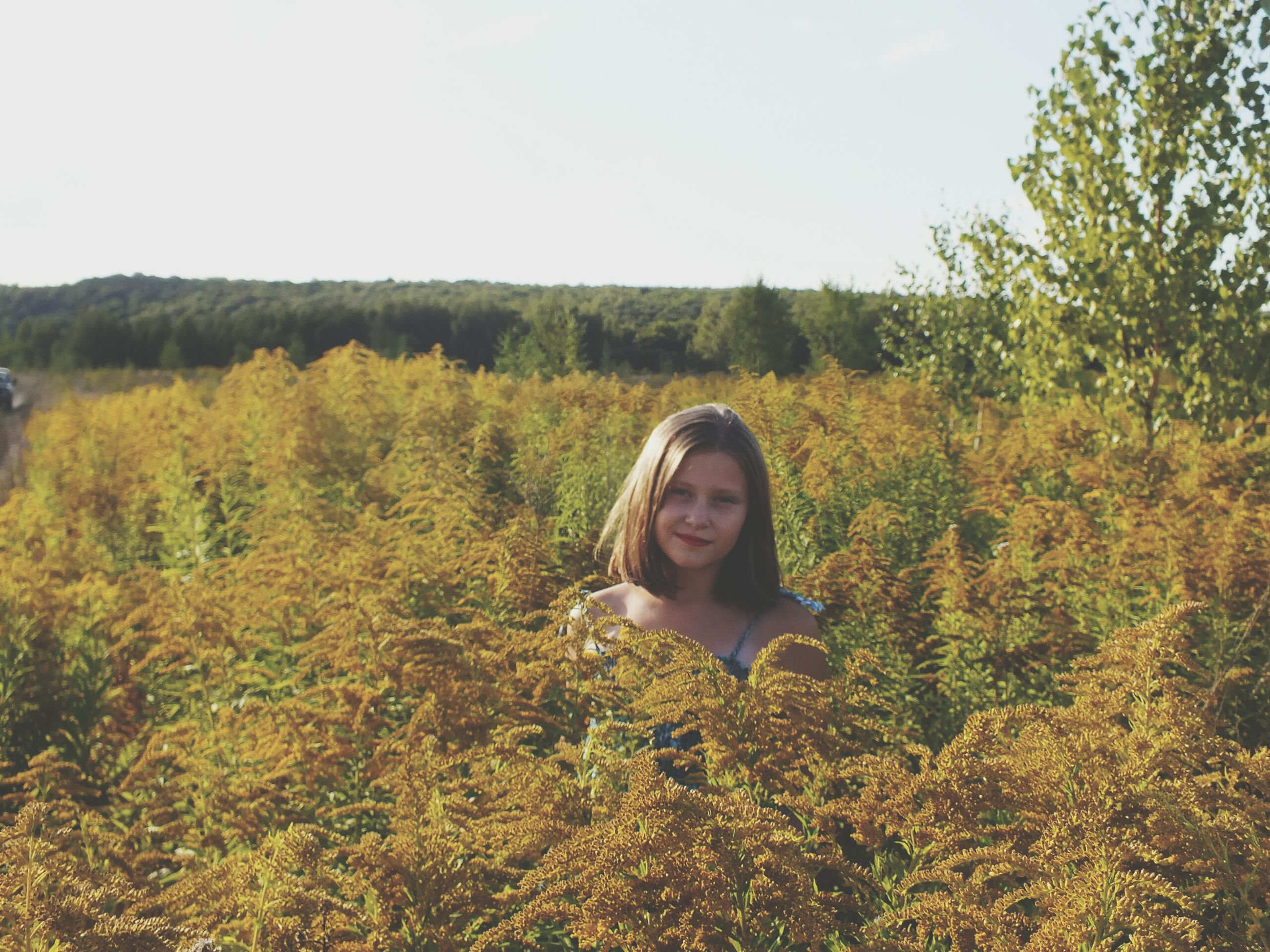 young adult, person, lifestyles, looking at camera, portrait, leisure activity, casual clothing, field, young women, tree, growth, front view, smiling, plant, standing, nature, clear sky, grass