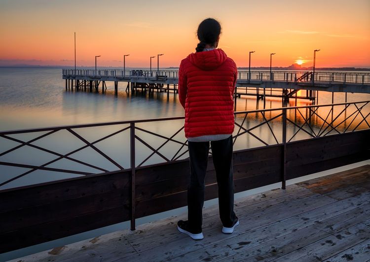 Rear view of man standing by railing against sea during sunset