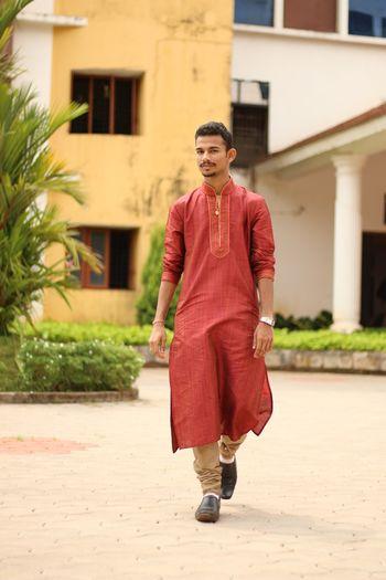 Full length portrait of young man in kurta walking against building