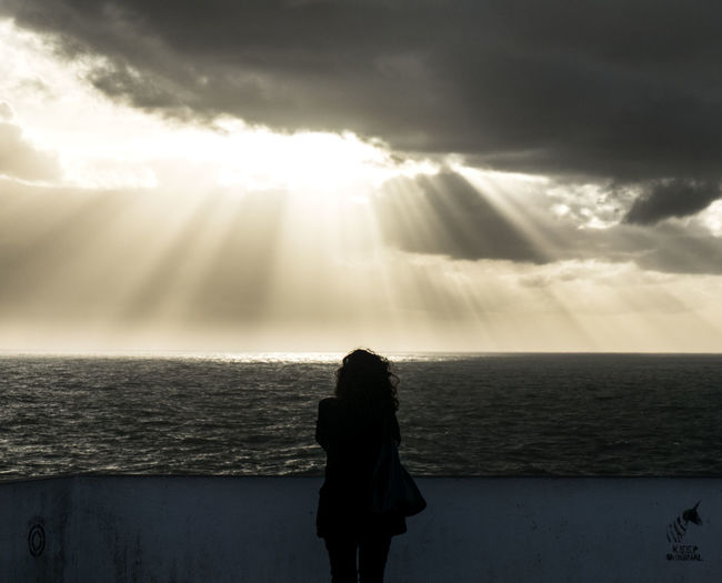 Silhouette Woman Standing On Sea Shore Against Sunbeam Streaming Through Cloudy Sky During Sunset