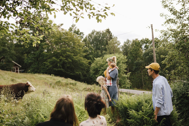 People standing on land by trees against sky