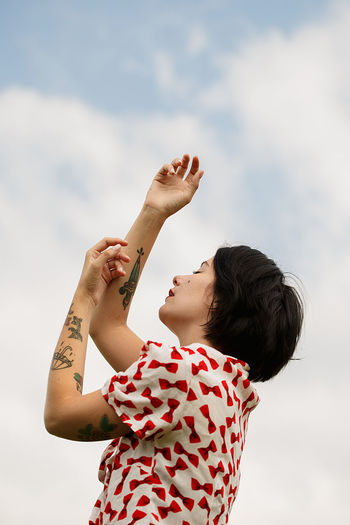 Low angle view of woman with tattoo on hands against sky