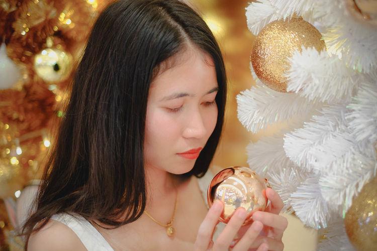 Close-up of woman looking at christmas tree