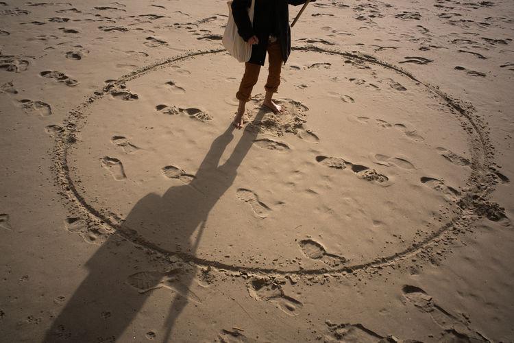 Woman drow a circle on beach